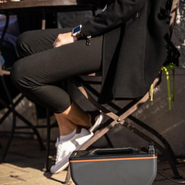 Akku von Super Soco CUX beim Laden im Hintergrund Frau auf Stuhl