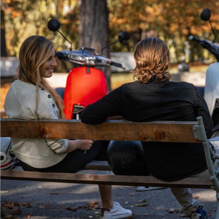 zwei Personen auf Parkbank mit roter Super Soco CUX im Hintergrund