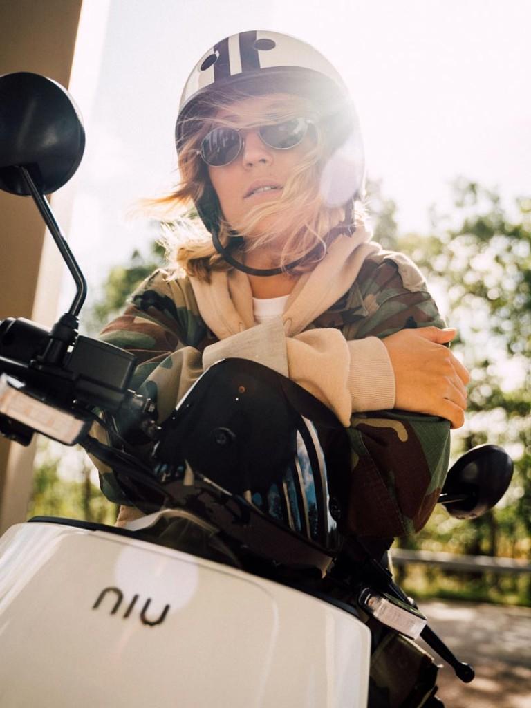 Mädchen auf weißem NIU Elektroroller mit Helm