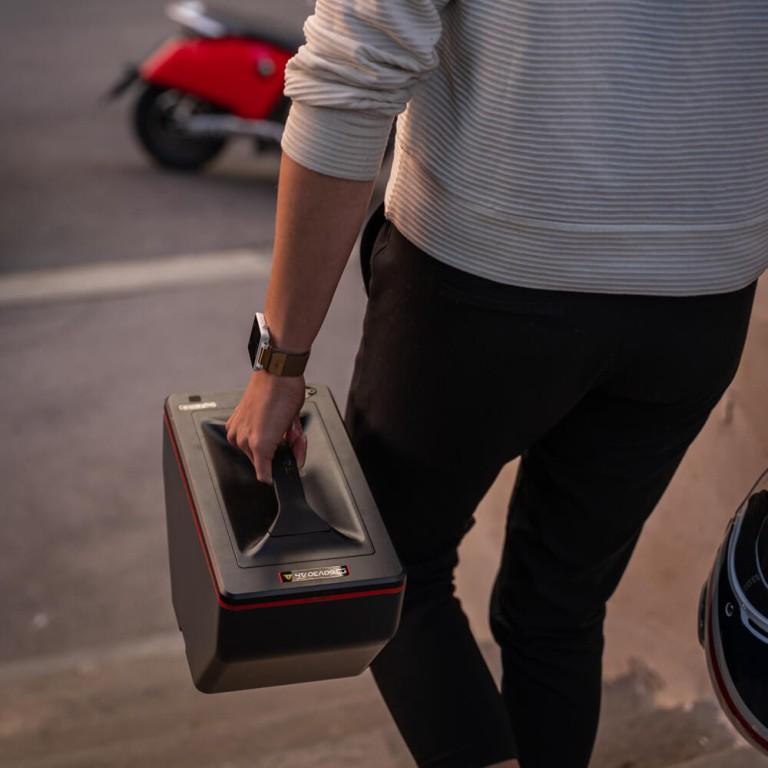 Akkupack für Elektroroller Super Soco CUX getragen von Person