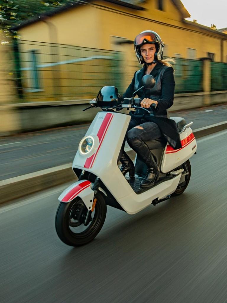 fahrender Elektroroller NIU NQiGT weiss mit roten Streifen mit blonder Fahrerin