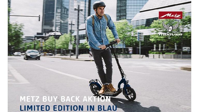 eScooter Metz Moover in blau mit Mann in Jeanshemd bei der Fahrt