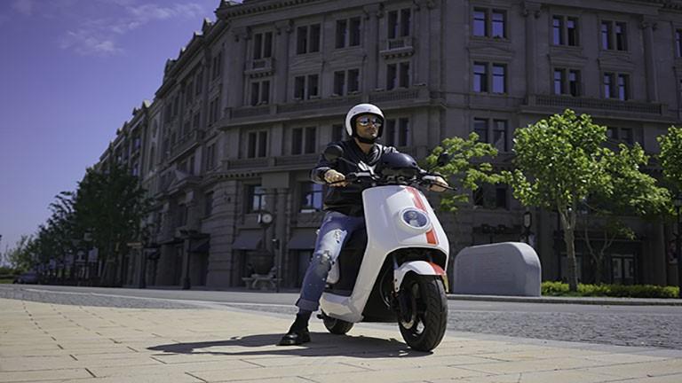 NIU NGT Elektroroller in weiss mit roten Streifen und Mann mit weißem Helm
