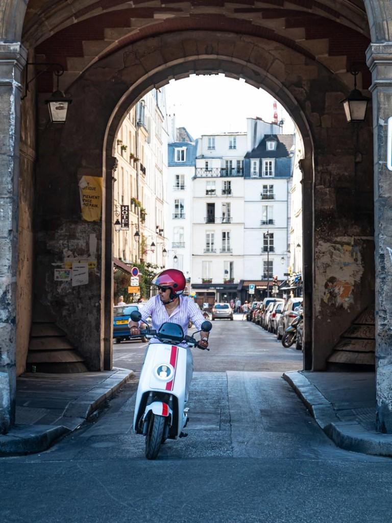 Elektroroller NIU NQiGT weiss mit roten Streifen in Altstadt von Italien