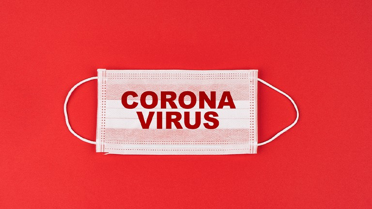 Corona Virus Maske auf rotem Hintergrund
