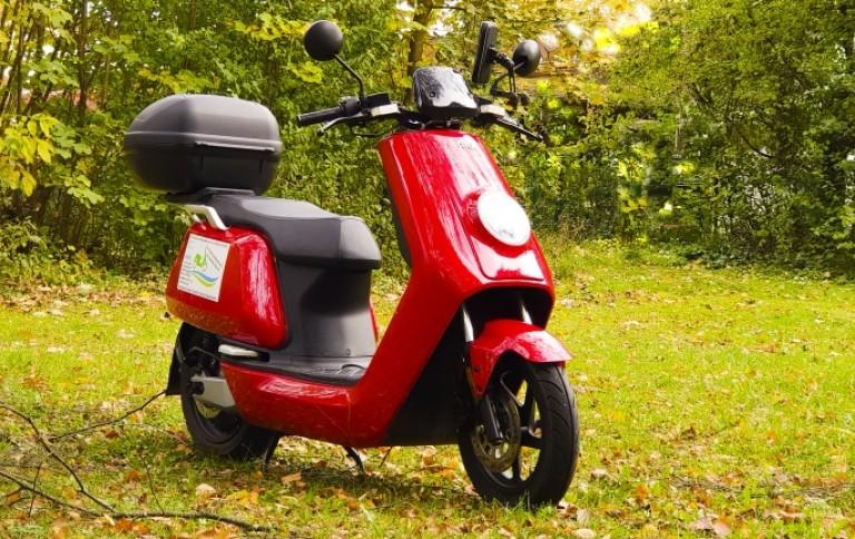 Elektroroller NIU N Sport rot im Herbstwald seitliche Frontansicht